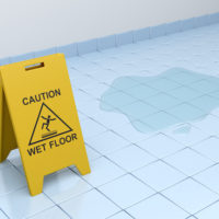 wet floor caution sign on tiled floor