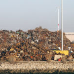 Pile of trash at Recycling processing facility along shore of Oakland Harbor, California during the day.