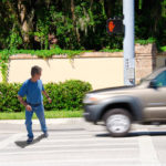 A man is jaywalking across an intersection when the signal is clearly showing the do not cross symbol.