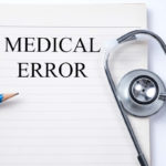 Stethoscope on notebook and pencil with Medical Error words