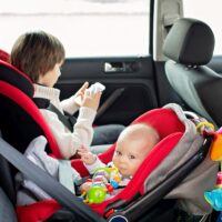 Little baby boy and his older brother, traveling in car seats, going on a holiday