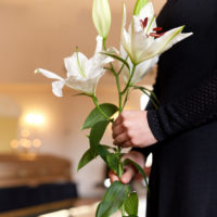 Wrongful Death Case concept close up of woman with lily flowers at funeral
