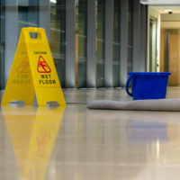 slip and fall accident concept Yellow caution sign showing warning of slippery wet floor